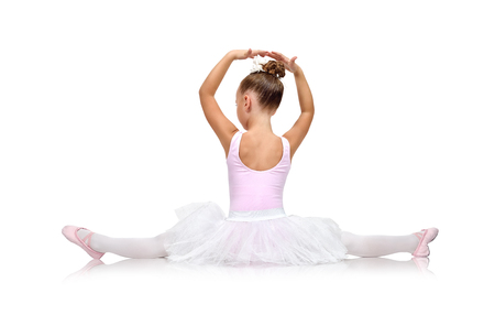 young girl: little ballerina in tutu sitting on floor, back view