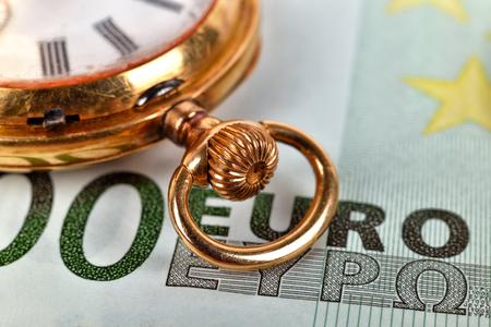 savings and loan crisis: golden pocket watch and euro bills, extra close up Stock Photo