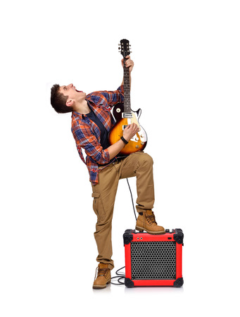 amp: expressive rocker man playing an electric guitar with combo amp Stock Photo