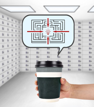 lockbox: hand holding disposable coffee cup with maze, path to success