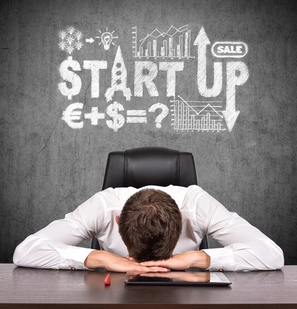 success man: tired businessman sitting at table and drawing start up concept over head Stock Photo