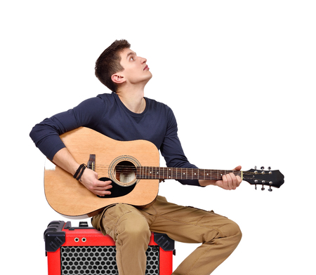 amp: man playing on acoustic guitar sitting on red combo amp