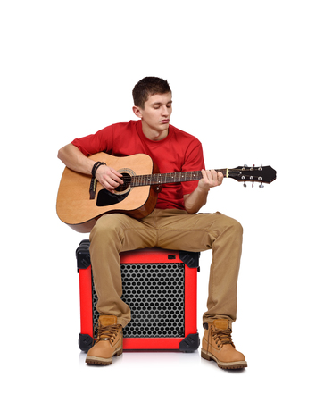 amp: man playing on acoustic guitar sitting on combo amp