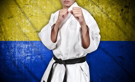 ukraine flag: karate fighter in white kimono on ukraine flag background Stock Photo