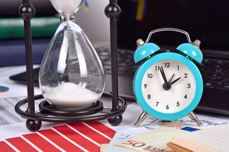 stock predictions: Sandglass, alarm clock and finansical report on table, close up