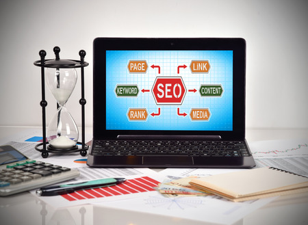 stock predictions: Seo scheme on screen laptop. Financial and business charts and report on table