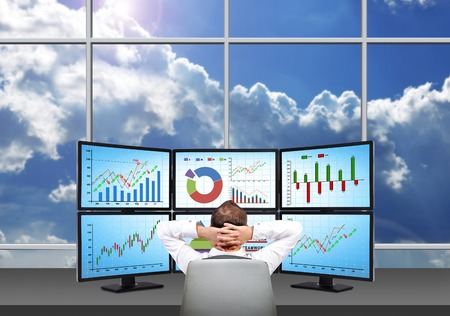 relaxing trader who is sitting in front of a trading station which consists of four screens with financial data.