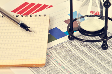 stock predictions: sandglass and business charts and report on table, vintage effect Stock Photo