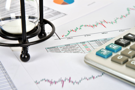 stock predictions: sandglass, financial and business charts and report on table Stock Photo