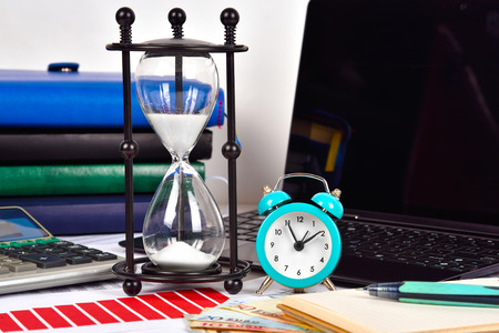 stock predictions: Alarm clock, Sandglass and finansical report on table, close up Stock Photo
