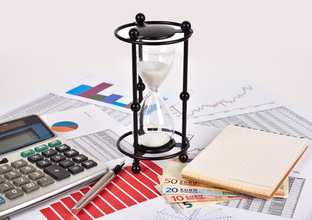 stock predictions: sandglass and business charts with report on table Stock Photo