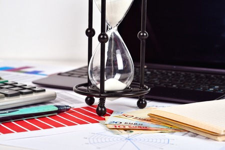 stock predictions: Business report and charts on table. Sandglass, money, calculator and laptop