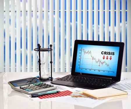stock predictions: Crisis chart on screen notebook. Financial and business charts and report on table Stock Photo