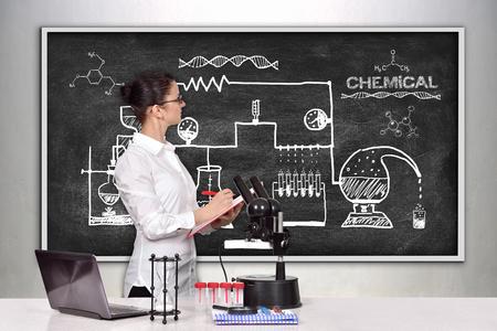 la femme chercheur scientifique en laboratoire et en regardant sur le tableau noir avec le dessin régime réaction chimique