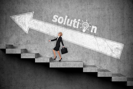 corporate women: Businesswoman with briefcase walking up on stairs. Drawing white arrow on wall. Solution concept