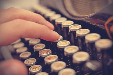 maquina de escribir: Mano que pulsa en la máquina de escribir vieja, con un efecto retro