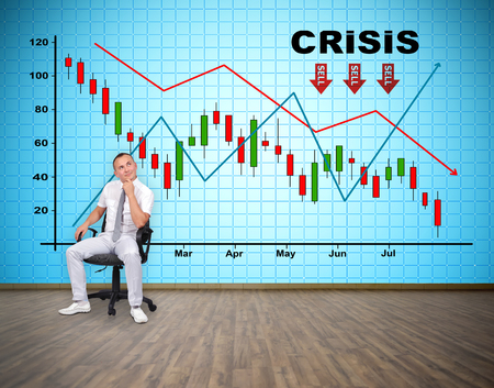 tv wall: businessman sitting in room and thinking. big plasma tv wall with crisis chart