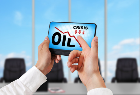 portable failure: hand holding digital tablet pc with oil crisis chart Stock Photo