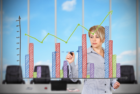 businesswoman standing in office and drawing stock chart photo