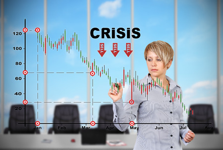young businesswoman standing in office and drawing crisis chart photo