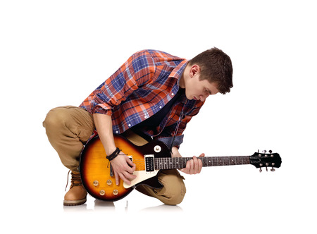 lead guitar: musician kneels with electric guitar on white background