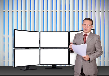 trader with paper standing near trading station which consists of six blank screens photo