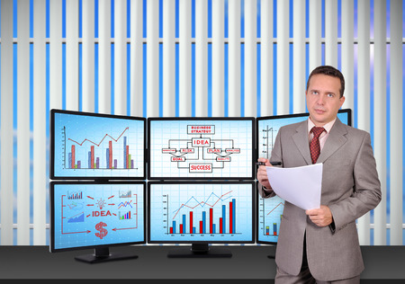 businessman standing near trading station which consists of six screens with financial data. photo