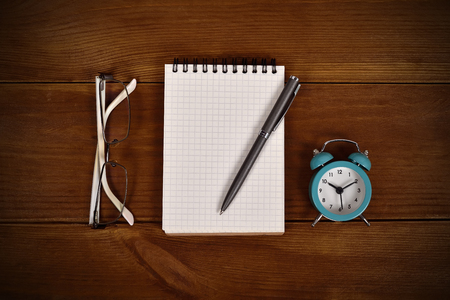 note pad and pen: blank note pad, pen, clock and glasses on wooden table