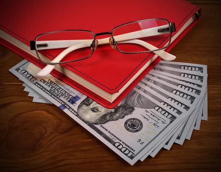 red bills: red leather diary, glasses and dollar bills on wooden desk Stock Photo