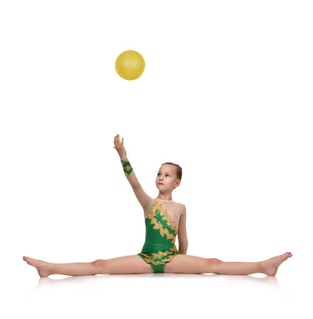 Little girl gymnast sitting on split and catches a ball