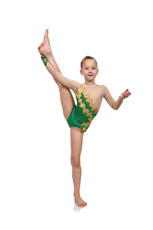 green clothes: Little girl gymnast in green clothes raised her leg up Stock Photo