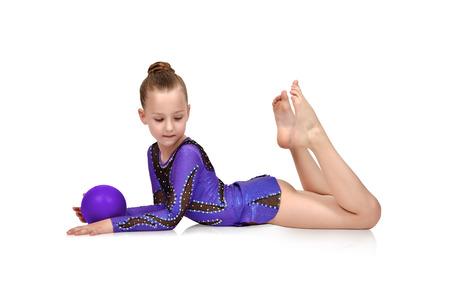 小さな女の子体操青いボールでポーズ