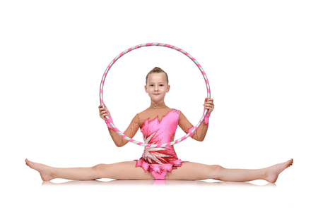Little girl in pink clothes with hula hoop doing gymnastics