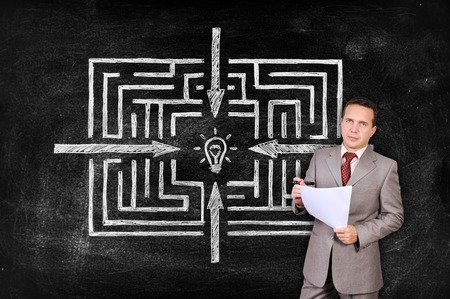 businesswoman with paper and drawing labyrinth to success on blackboard photo