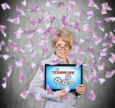 businesswoman holding tablet with teamwork concept and flying euro banknote photo