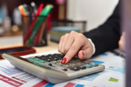 considers: accountant woman considers on the calculator profit close up Stock Photo