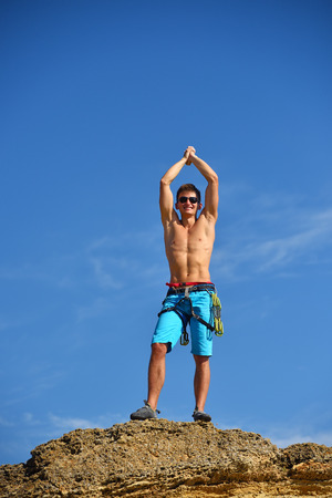 Male Climber Raising Hands On The Top Of Mountain.   Concept Of Success