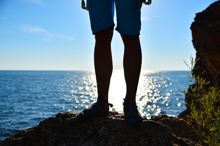 foot climber on a cliff, sunsen in ocean on background Stock Photo