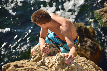 Male climber climbs on rocky wall. View from above Stock Photo