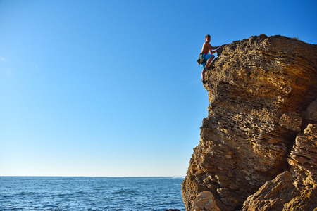 Young male rock climber on yellow mountain.