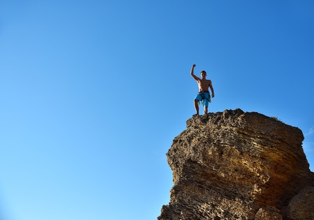 Climber Raising Hand On Top Of Mountain.   Concept Of Success
