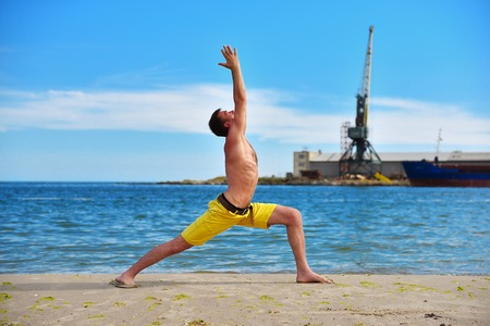 acts: caucasian man acts yoga on beach in day