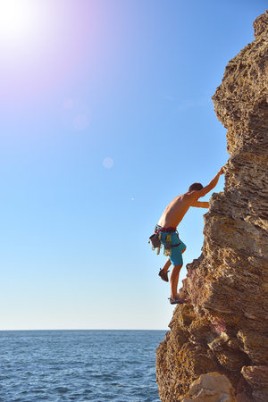 clambering: Young man climbing up on yellow mountain on sea background