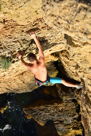 male rock climber climbs on rocky wall, view from above Stock Photo