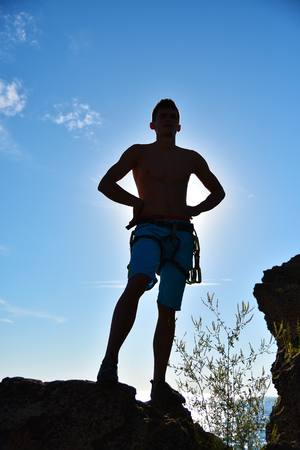 extreme climber on a cliff, sunsen in ocean on background