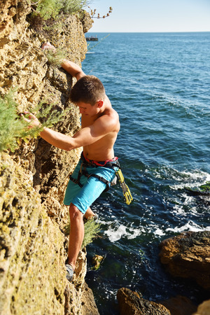 rockclimber: Male climber climbs on rocky wall. View from above Stock Photo