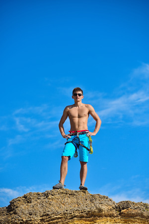 rockclimber: athletic climber man standing on top mountain