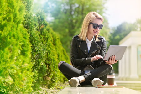 happy hipster girl sitting with laptop in hand