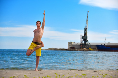 prana: man making yoga exercises on harbor crane background