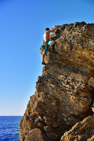 Young man climbing up on yellow mountain on a sea background